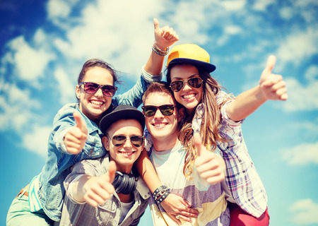 Photo for summer holidays and teenage concept - group of smiling teenagers in sunglasses hanging outside and showing thumbs up - Royalty Free Image