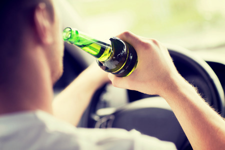 Photo for transportation and vehicle concept - man drinking alcohol while driving the car - Royalty Free Image