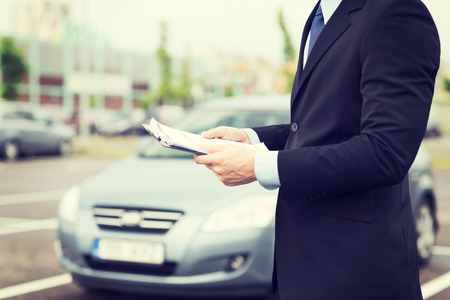 Photo pour transportation and ownership concept - man with car documents outside - image libre de droit