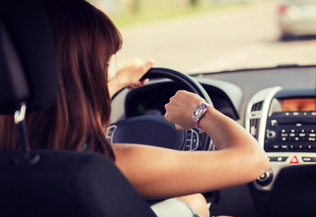 Photo pour transportation and vehicle concept - woman driving a car and looking at watch - image libre de droit