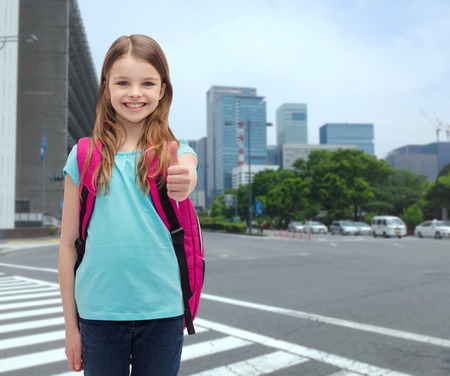 Photo for education, gesture and school concept - happy and smiling little girl with school bag showing thumbs up - Royalty Free Image