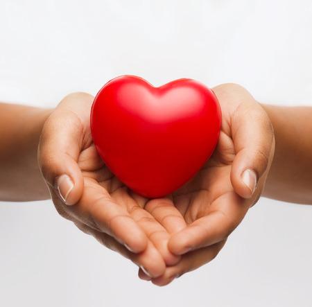 Foto de health, medicine and charity concept - close up of african american female hands with small red heart - Imagen libre de derechos