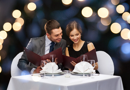 Foto de restaurant, couple and holiday concept - smiling couple with menus at restaurant - Imagen libre de derechos