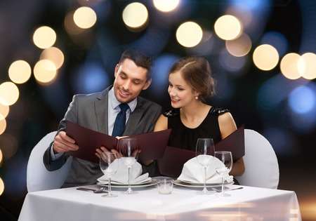 Photo pour restaurant, couple and holiday concept - smiling couple with menus at restaurant - image libre de droit