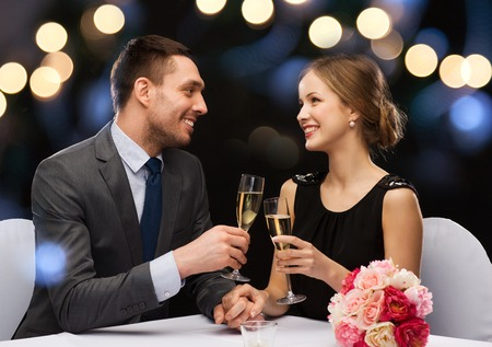 Photo for restaurant, couple and holiday concept - smiling couple with glass of champagne looking at each other at restaurant - Royalty Free Image