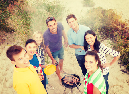Photo for summer, holidays, vacation, happy people concept - group of friends having picnic and making barbecue on the beach - Royalty Free Image