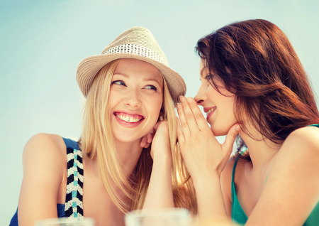 Photo for summer holidays and vacation concept - girls gossiping in cafe on the beach - Royalty Free Image