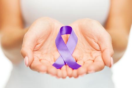Photo pour healthcare and social problems concept - womans hands holding purple domestic violence awareness ribbon - image libre de droit
