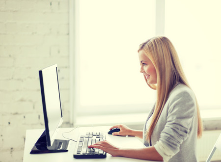 Foto de picture of smiling businesswoman with computer in office - Imagen libre de derechos