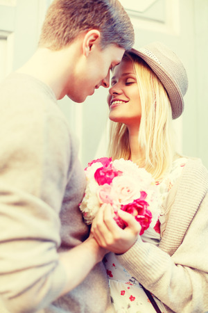 Foto de summer holidays, love, relationship and dating concept - happy couple with bouquet of flowers in the city - Imagen libre de derechos
