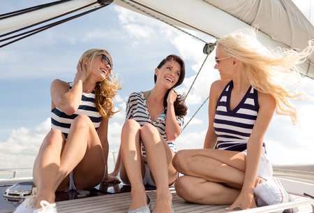 Foto de vacation, travel, sea, friendship and people concept - smiling girlfriends sitting on yacht deck - Imagen libre de derechos