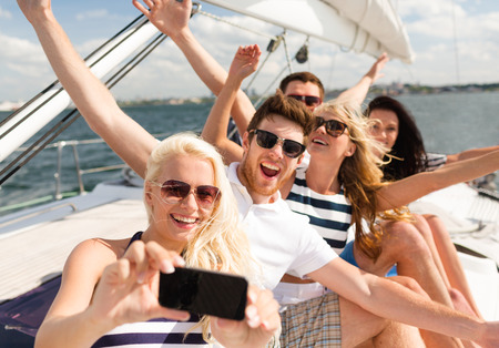 Foto de vacation, travel, sea, friendship and people concept - smiling friends sitting on yacht deck and making selfie - Imagen libre de derechos