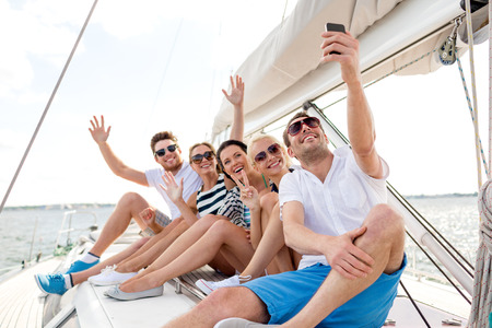 Photo for vacation, travel, sea, friendship and people concept - smiling friends sitting on yacht deck and making selfie - Royalty Free Image