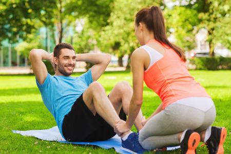 Foto de fitness, sport, training, teamwork and lifestyle concept - smiling man with personal trainer doing exercises on mat outdoors - Imagen libre de derechos