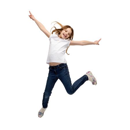Foto de happiness, activity and child concept - smiling little girl jumping - Imagen libre de derechos
