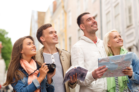 Photo pour travel, vacation, technology and friendship concept - group of smiling friends with city guide, photocamera and map exploring city - image libre de droit