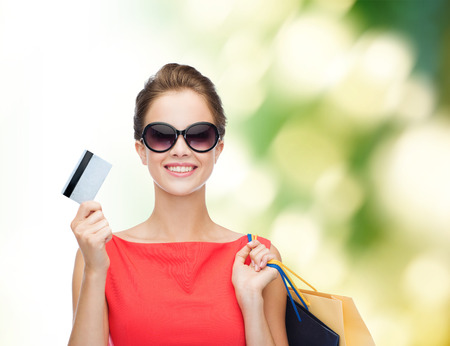 Photo pour shopping, sale, christmas and holiday concept - smiling elegant woman in red dress with shopping bags and plastic card - image libre de droit