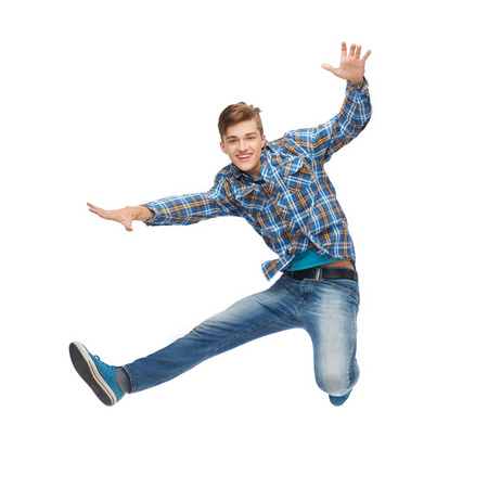 Foto de happiness, freedom, movement and people concept - smiling young man jumping in air - Imagen libre de derechos