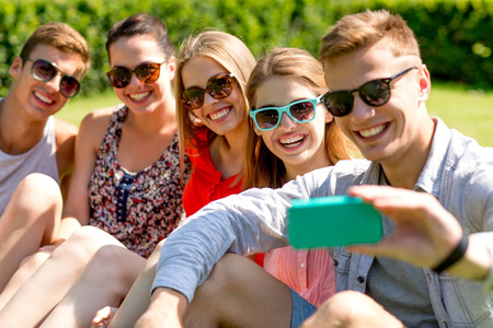 Photo for friendship, leisure, summer, technology and people concept - group of laughing friends with smartphone making selfie in park - Royalty Free Image
