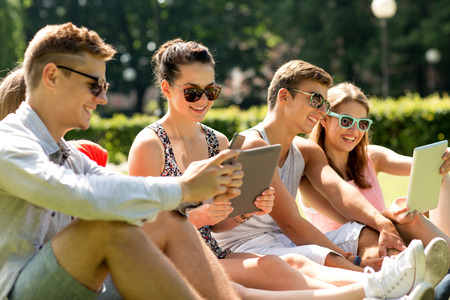 Foto de friendship, leisure, summer, technology and people concept - group of smiling friends with tablet pc computers and smartphone sitting on grass in park - Imagen libre de derechos
