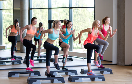 Foto de fitness, sport, training, gym and lifestyle concept - group of women working out with steppers in gym - Imagen libre de derechos