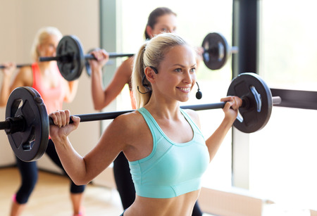 Foto de fitness, sport, training and lifestyle concept - group of women with barbells in gym - Imagen libre de derechos