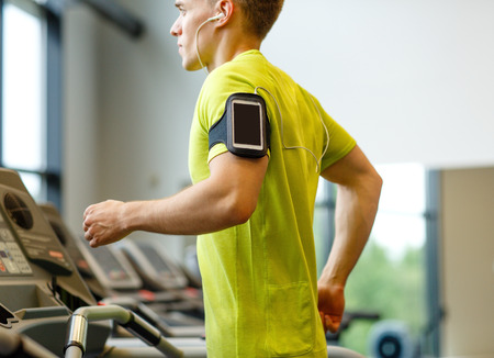 Foto de sport, fitness, lifestyle, technology and people concept - man with smartphone and earphones exercising on treadmill in gym - Imagen libre de derechos