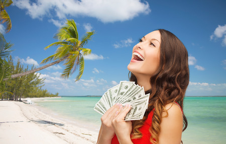 Foto de christmas, x-mas, sale, banking and travel concept - smiling woman in red dress with us dollar money over tropical beach background - Imagen libre de derechos