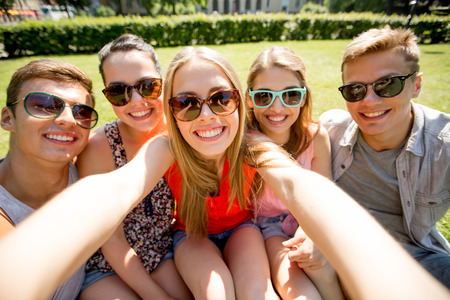 Photo for friendship, leisure, summer, technology and people concept - group of smiling friends making selfie with smartphone camera or tablet pc in park - Royalty Free Image
