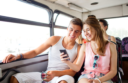 Foto de friendship, summer vacation, transport, technology and people concept - smiling couple with smartphone traveling by bus and making selfie - Imagen libre de derechos