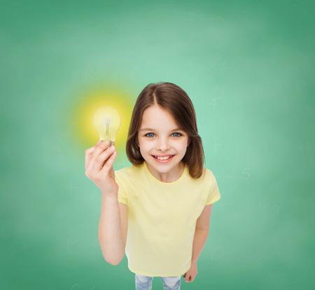 Foto de electricity, education and people concept - smiling little girl holding light bulb - Imagen libre de derechos