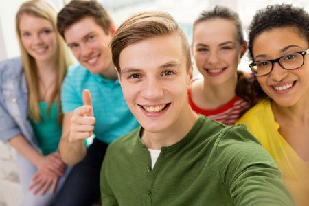 Photo for education, leisure and technology concept - five smiling students taking selfie at school - Royalty Free Image