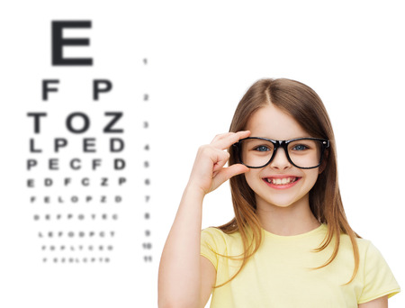 Photo for education, school and vision concept - smiling cute little girl in black eyeglasses - Royalty Free Image