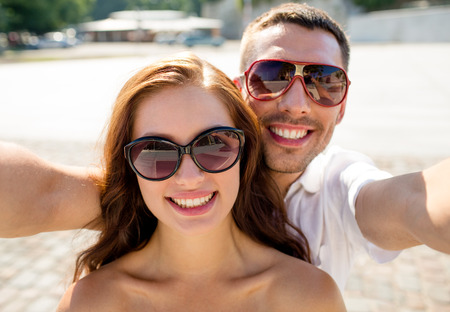 Photo pour love, wedding, summer, dating and people concept - smiling couple wearing sunglasses making selfie in city - image libre de droit