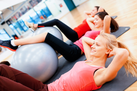 Foto de fitness, sport, training, gym and lifestyle concept - group of smiling people working out in pilates class - Imagen libre de derechos
