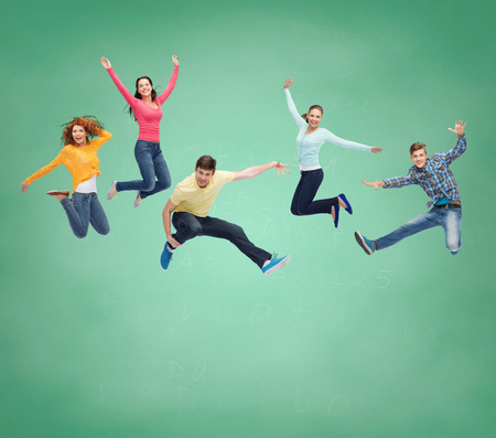 Foto de happiness, freedom, friendship, education and people concept - group of smiling teenagers jumping in air over green board background - Imagen libre de derechos