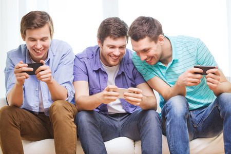 Photo for friendship, technology and home concept - smiling male friends with smartphones at home - Royalty Free Image
