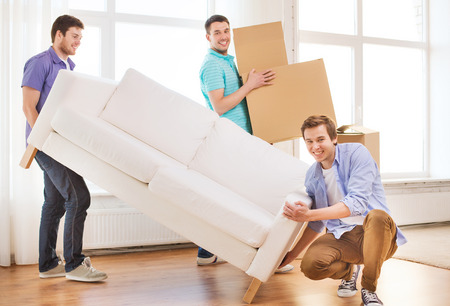 Photo for repair, furniture, decorating and home concept - smiling friends with sofa and cardboard boxes - Royalty Free Image
