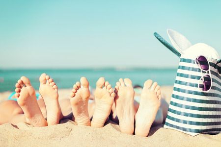Foto de summer vacation, sunbathing and pedicure concept - three women lying on the beach with straw hat, sunglasses and bag - Imagen libre de derechos