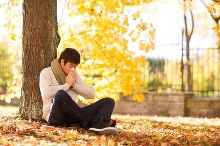 Foto de season, technology and people concept - smiling young man with tablet pc computer in autumn park - Imagen libre de derechos