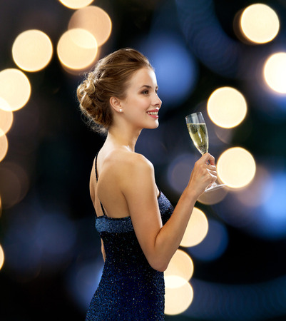 Photo for party, drinks, holidays, luxury and celebration concept - smiling woman in evening dress with glass of sparkling wine over night lights background - Royalty Free Image