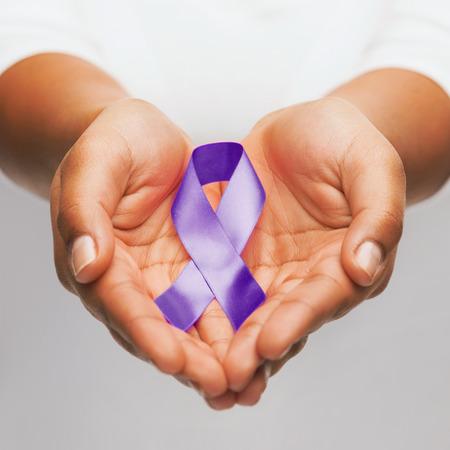 Foto de healthcare and social problem concept - womans hands holding purple domestic violence awareness ribbon - Imagen libre de derechos
