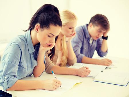 Foto de school and education concept - group of tired students with notebooks at school - Imagen libre de derechos