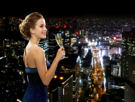 Photo pour party, drinks, holidays, luxury and celebration concept - smiling woman in evening dress with glass of sparkling wine over night city background - image libre de droit