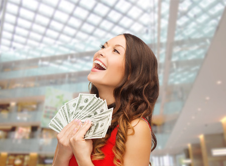 Foto de christmas, x-mas, shopping, banking and people concept - smiling woman in red dress with us dollar money over shopping centre background - Imagen libre de derechos