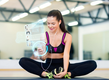 Photo pour fitness, sport, training, technology and lifestyle concept - smiling young woman with smartphone and earphones in gym - image libre de droit