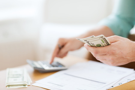 Foto de savings, finances, economy and home concept - close up of man with calculator counting money and making notes at home - Imagen libre de derechos