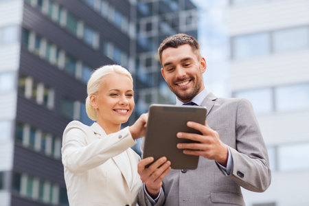 Photo for business, partnership, technology and people concept - smiling businessman and businesswoman with tablet pc computer over office building - Royalty Free Image