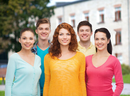 Photo for friendship, education, summer vacation and people concept - group of smiling teenagers standing over campus background - Royalty Free Image