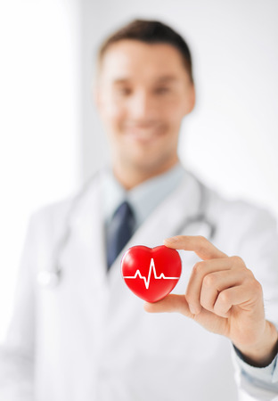 Foto de healthcare and medicine concept - male doctor holding red heart with ecg line - Imagen libre de derechos